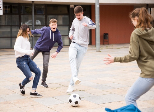 Cheerful schoolchildren are playing football in the school yard during a break in casual clothes