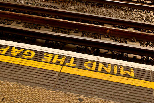 An industrial rustic weather gritty textured railway london tube mind the gap floor font. rough textured cement flooring