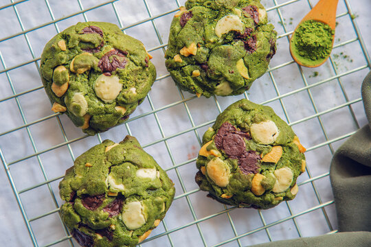 high angle matcha cookies on a cooling rack on white table with macha powder on a wooden spoon