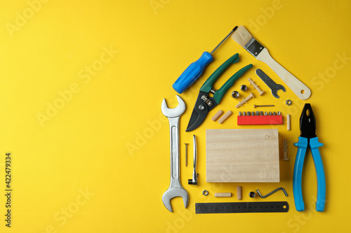 House made of working tools on yellow background