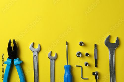 Flat lay with working tools on yellow background