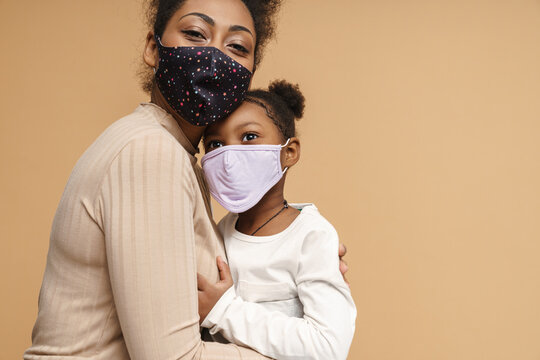 Black mother and daughter in face mask hugging and looking at camera