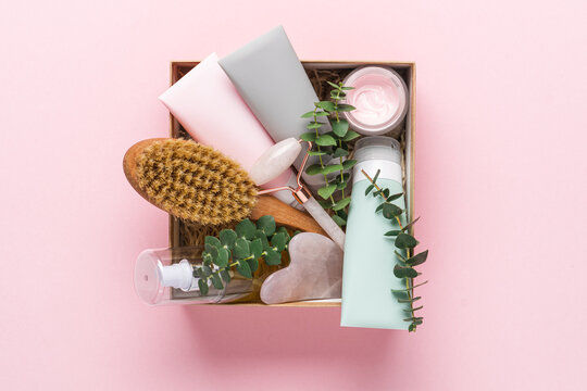 Beauty box with face and body care products on pink background. Tubes with cream and lotion, hydrophilic oil, facial roller, guache massager, body brush. Natural cosmetics gift