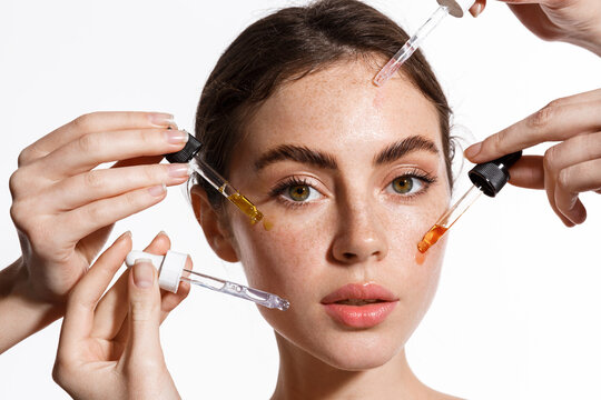 Beauty face of woman with freckles, natural clean and fresh glowing skin, apply anti-aging collagen serum. Hands holding serum with active botanical ingredients vitamin c in dropper, white background
