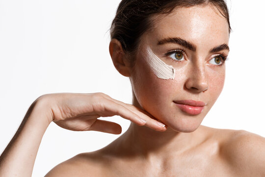 Beauty woman applying face cream on clean fresh skin, detoxifying effect, moisturize and hydrate facial with scrub, nourishing effect of mask, looking aside, white background