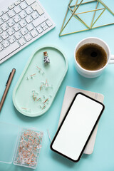 Lady freelancer's home pastel blue workplace, cup of coffee and smartphone mock-up on tabletop