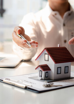 The real estate agent is explaining the house style to the clients who come to contact to see the house design and the purchase agreement.