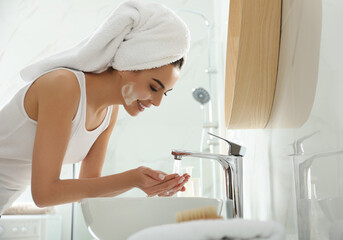 Happy young woman washing face in bathroom