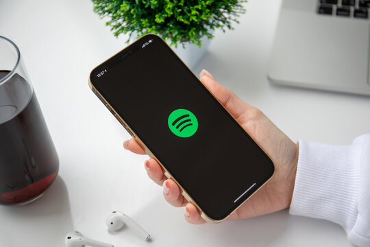 Woman holding iPhone 11 Pro Max Gold with service Spotify