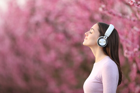 Woman relaxing listening to music with headphones in a pink field