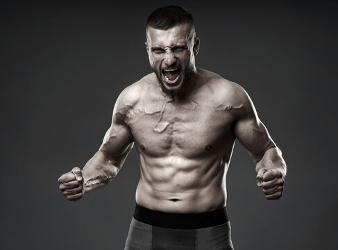 Athletic fighter posing on gray