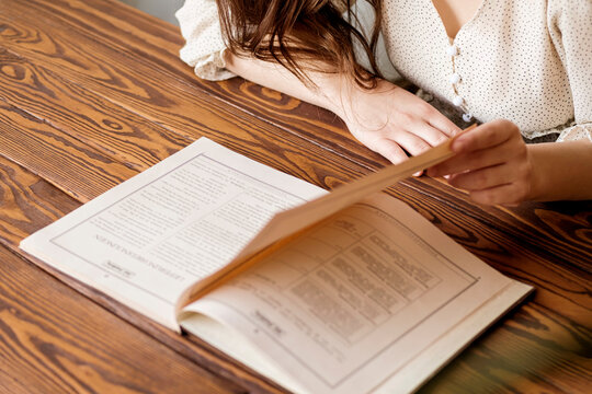 A woman in a light silk dress in the reading room is turning over the pages of a book