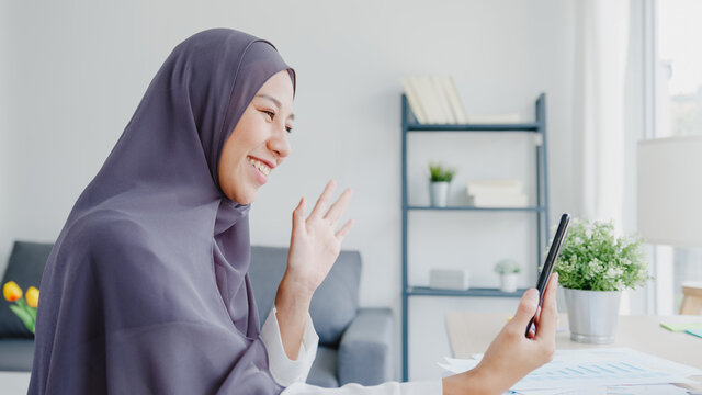 Young Asia muslim businesswoman using smart phone talk to friend by videochat brainstorm online meeting while remotely work from home at living room. Social distancing, quarantine for corona virus.