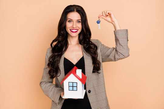 Photo of charming cute young lady dressed checkered blazer holding house keys isolated beige color background