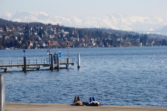 Women relax on the banks of Lake Zurich on a sunny spring day in Zurich
