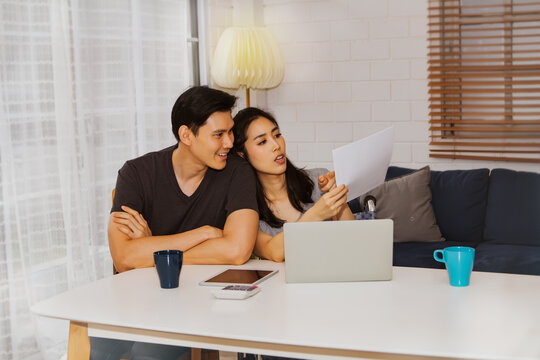 Asian couples work online together to discuss online trade papers and do household chores with their laptops.Look for the details, look at the whitepaper: Couples plan their business and work from hom