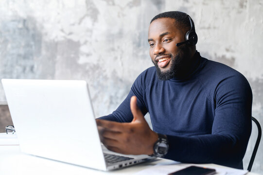 Friendly African-American male entrepreneur wearing wireless headset using a laptop for online communication with customers, a dark skinned employee using hands free device for video conversation