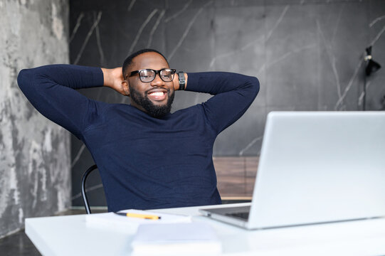 Relaxed African-American male entrepreneur leaned back in chair, holds hands behind head and rests after productive and successful day at work, satisfied black employee takes a break on the workplace