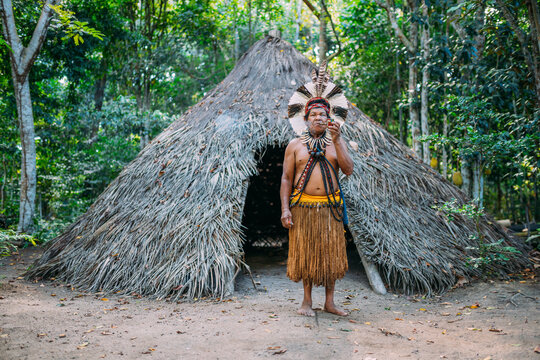Shaman of the Pataxó tribe, wearing feather headdress and smoking a pipe. Brazilian Indian looking at the camera