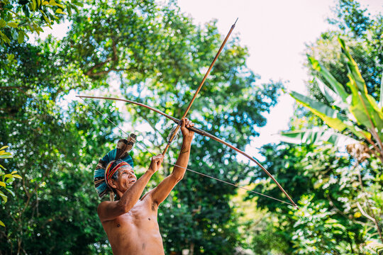 Indian from the Pataxó tribe, with a feather headdress and bow and arrow. Elderly Brazilian Indian