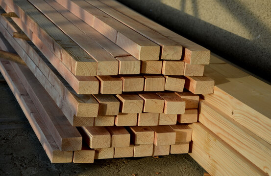 in the yard we work with wooden prisms to repair the roof. the saw formats them to the required dimensions and there are a lot of cuttings on the ground. The wooden beams are stacked in height