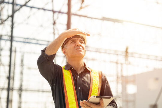 Foreman builder engineer worker looking at large building construction site sunny day hard work.