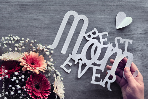 Mothers day greeting card design. Gerberas and white baby breath flowers on grey wood background. Flower arrangement, floral composition. Hand hold paper text Best Mom Ever. Happy Mother's day