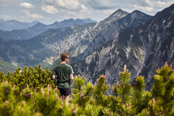 Young man standing on the summit Schildenstein in the Alps with shorts and T-shirt. In the...