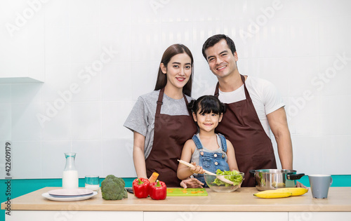 Portrait of little asian girl parents cooking preparing food with pan in the counter kitchen. Happy asian family with father mother daughter, mother's day, healthcare cooking plant based food concept