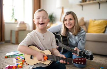 Single mother with down syndrome child at home, playing guitar.