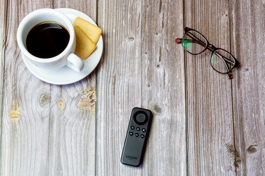 03-23-2021 Portsmouth, Hampshire, UK An amazon fire stick remote control laid on a wooden table next to a coffee and glasses