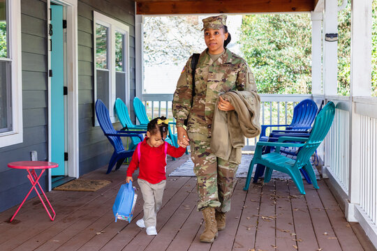 Black woman walking child to school, military personnel