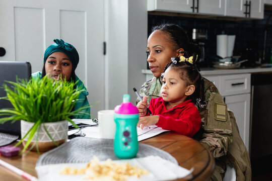 Black mother and daughter paying bills at home, soldier