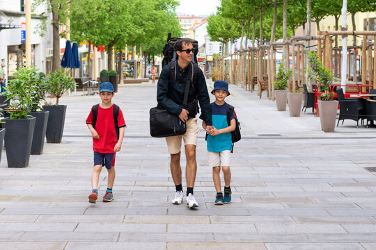 Father with children traveling, walking the street of a city with backpacks.