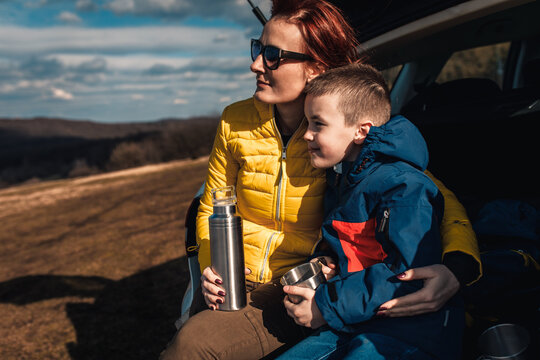 Mother and son take break from driving sitting by the car while drinking tea in nature.