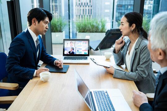 都心の企業で働くビジネスチームがオンライン会議を行っている