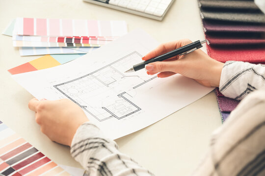 Female interior designer with house plan in office