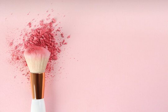 Makeup brush and scattered blush on pink background, top view. Space for text