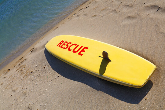 Close up yellow surfing board on sand sea beach