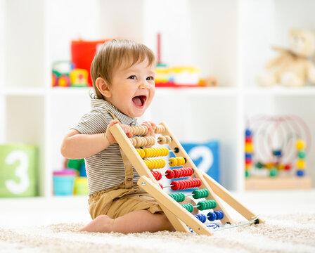 Little child boy playing with toy blocks. Baby in nursery or kindergarten