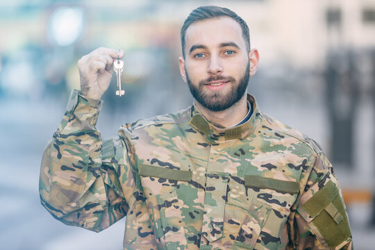 A soldier in camouflage uniforms shows house keys, mortgage assi