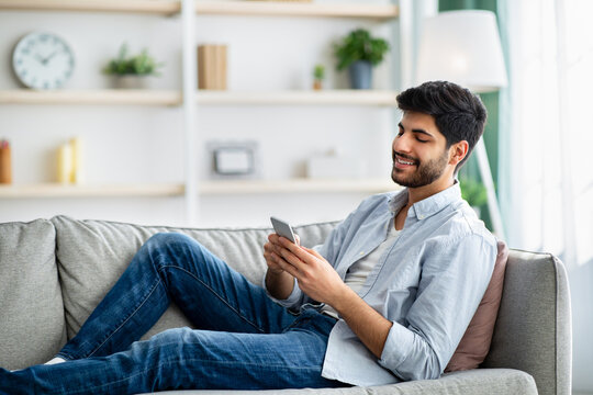 Mobile communication concept. Happy arab man using cellphone, browsing internet, sitting on couch at home, copy space