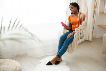 beautiful young african woman with mobile phone in the interior