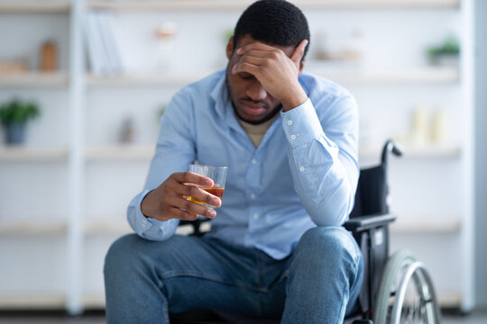Disability depression and alcohol abuse concept. Young handicapped man with drink sitting in wheelchair at home