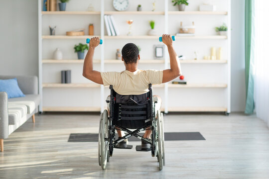 Back view of impaired black guy in wheelchair exercising with dumbbells at home. Sports and disability concept