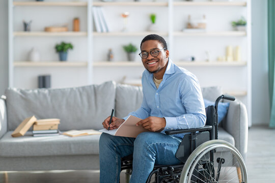 Happy disabled black guy in wheelchair taking notes, looking at camera and smiling at home, copy space