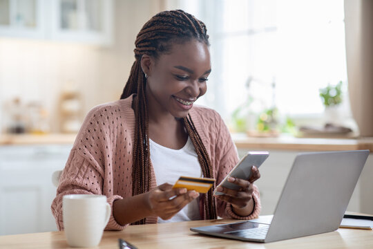 Online Payments. Cheerful black lady using smartphone and credit card in kitchen