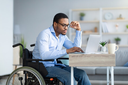 Focused young man in wheelchair using laptop computer for online work or communication at home