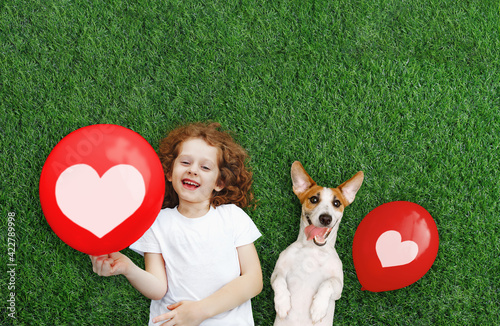 Laughing girl and puppy holding red balloon