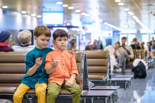 Two young brother boy dreaming of becoming a pilot. A child with a toy airplane plays at airport waiting for departure on their aircraft. Travel and holidays with children concept